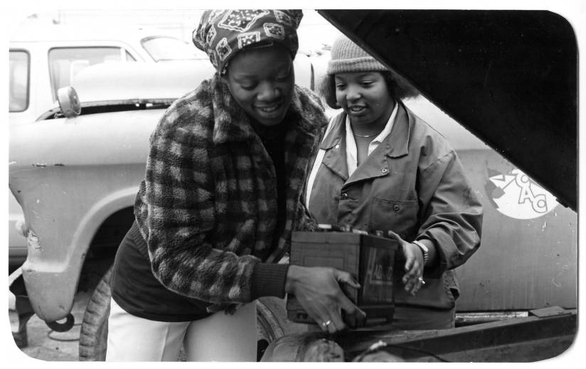 Two women putting car battery in car.